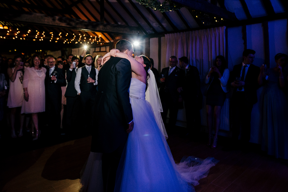 Bride and groom sharing dance together while guests watch