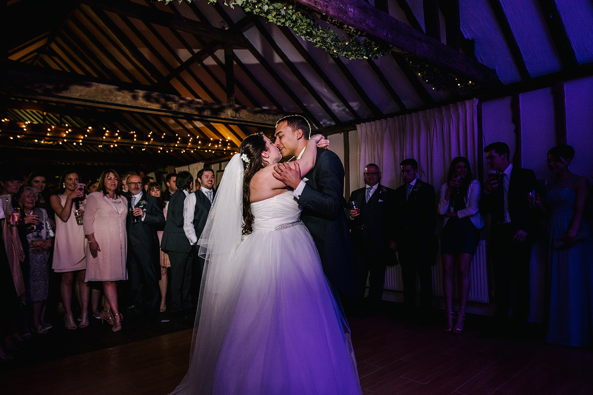 Bride and groom share a kiss while dancing
