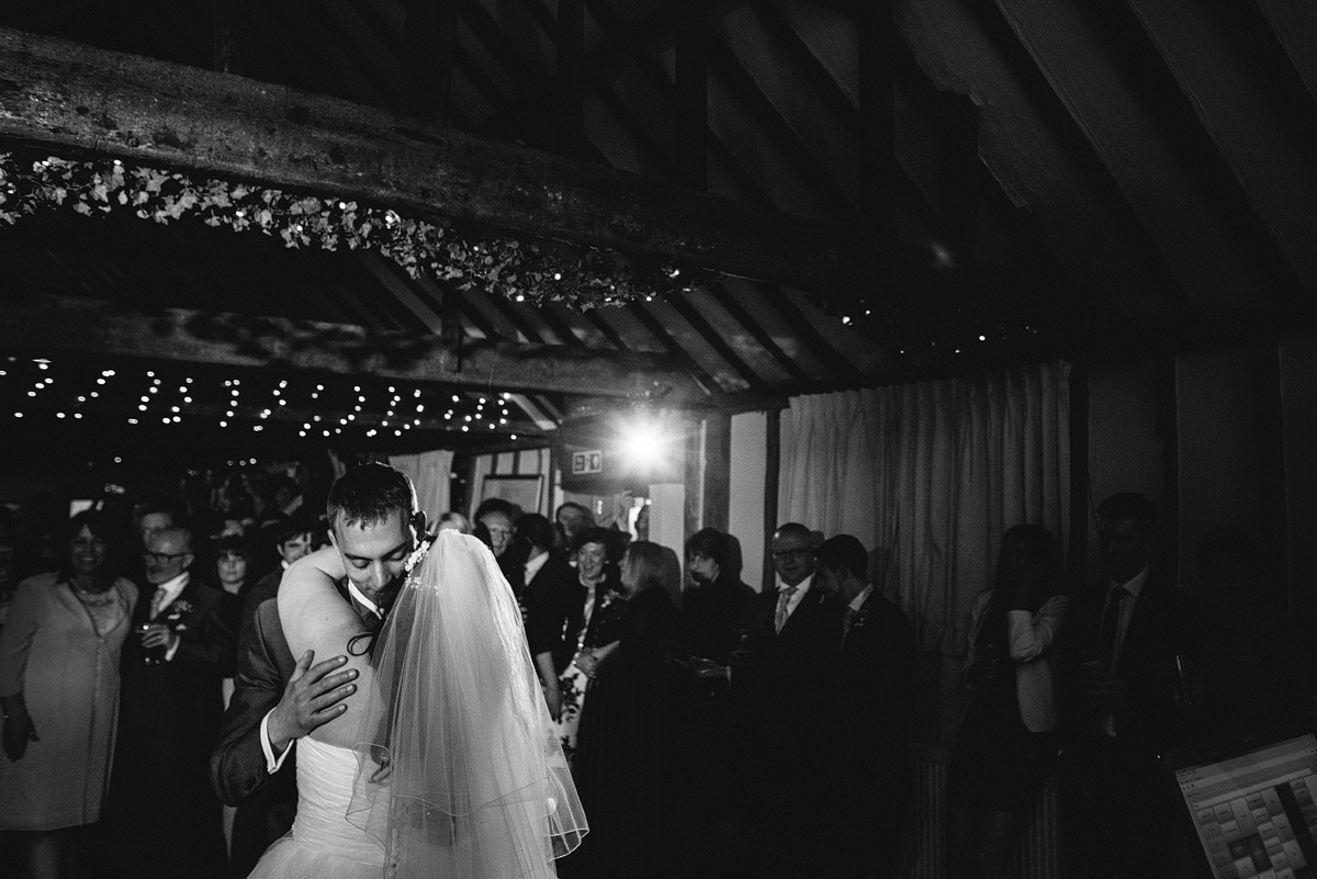 Black and white image of bride and groom dancing under lights in barn