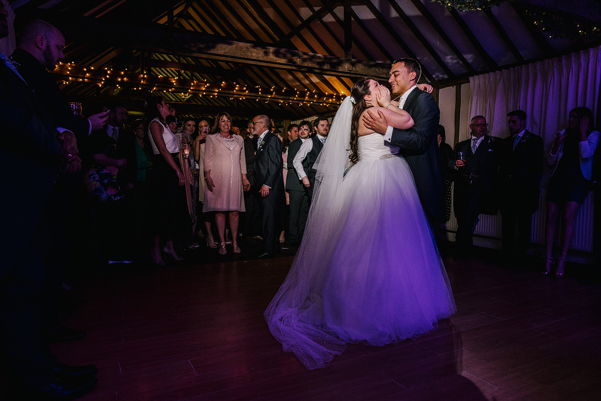 Bride and groom dancing while bride covers face
