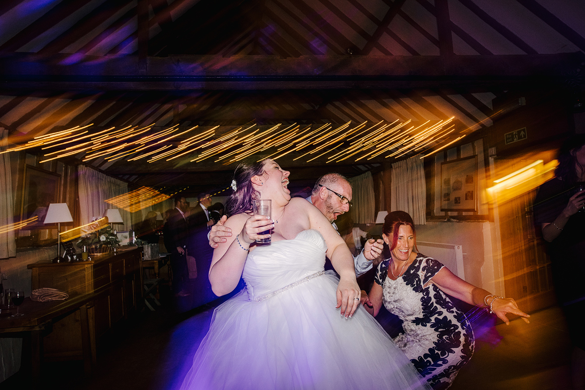 Bride dancing with guests while laughing, overexposed background lights