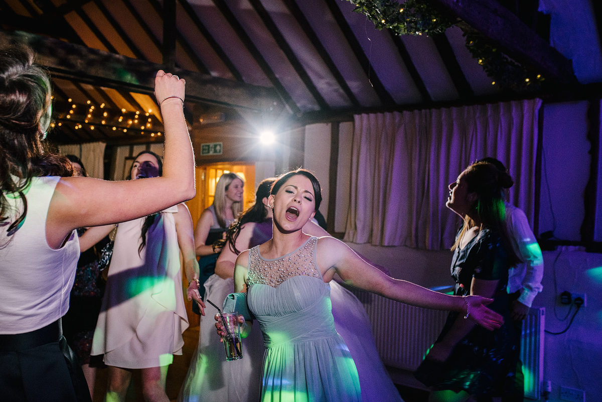 Bridesmaid singing and dancing with green lighting overhead