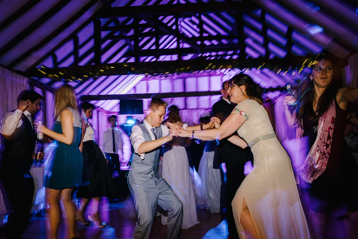 Guests dancing in barn with purple lights overhead