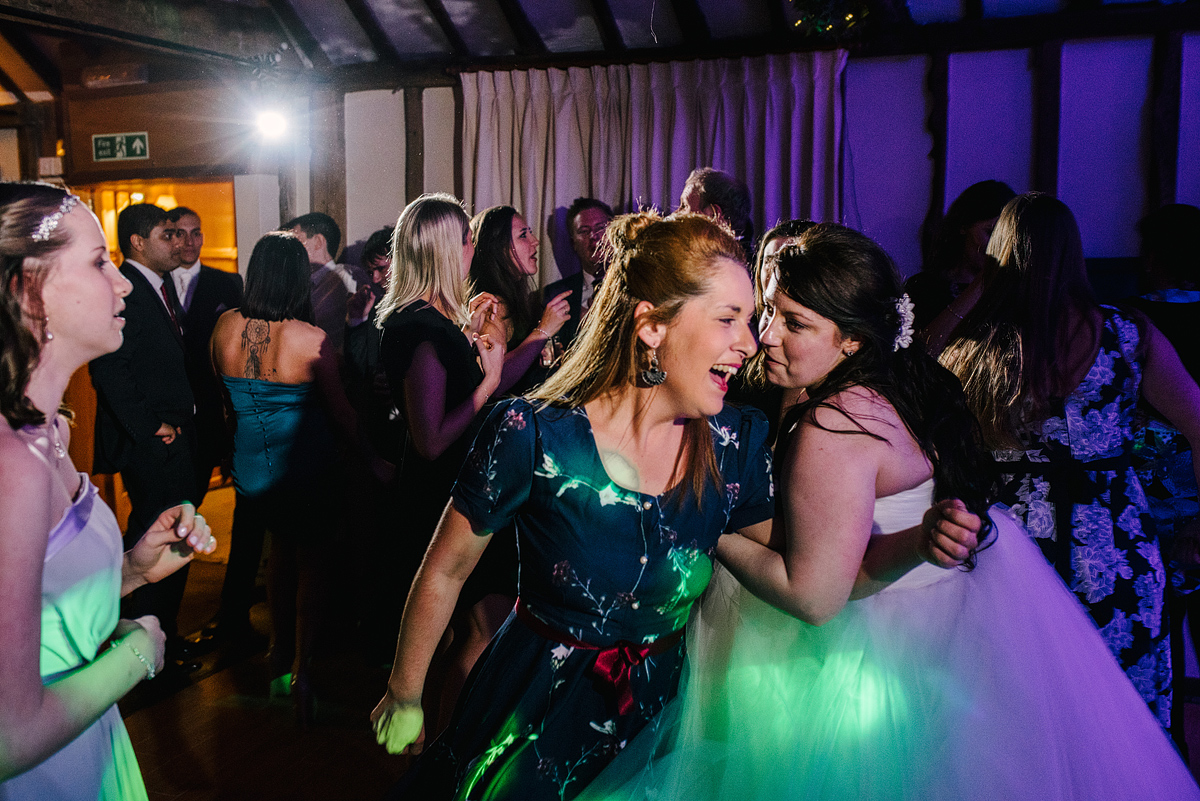 Bride and guest laughing with green and purple lights above
