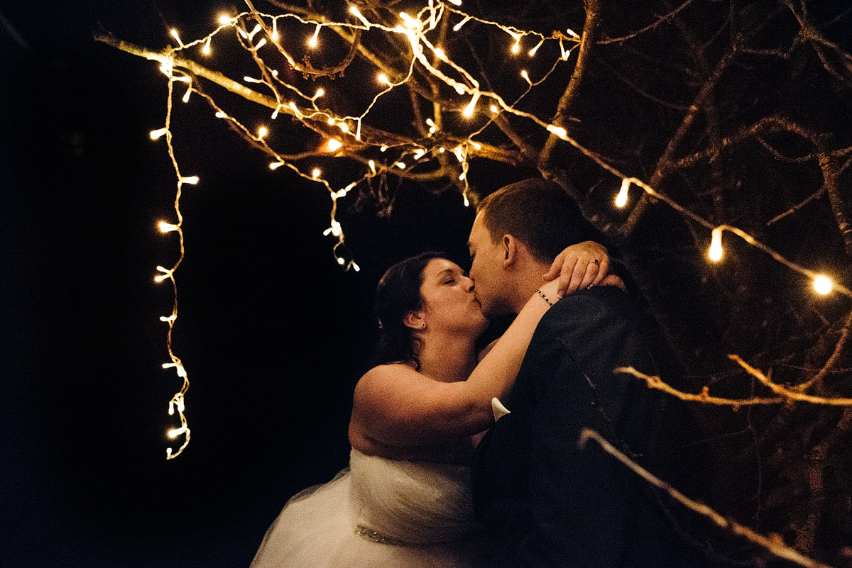 Bride and groom kissing outside at night under white lights