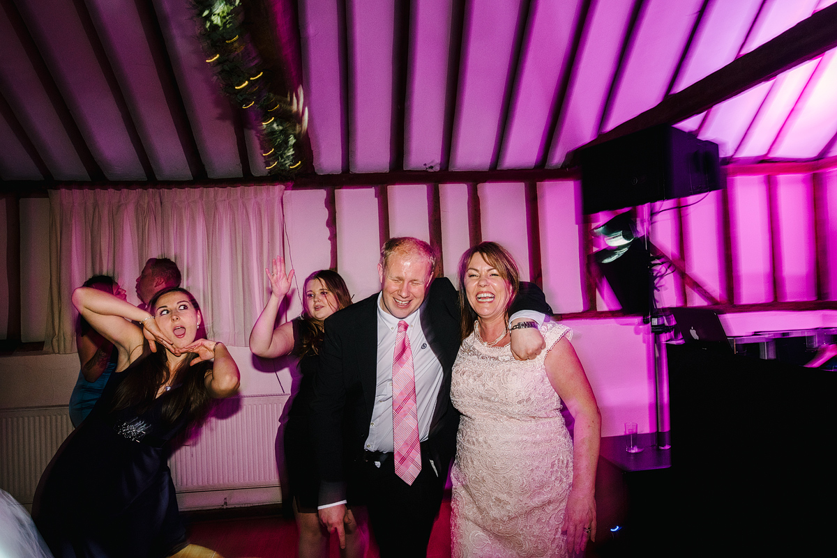 Guests laughing making silly faces under pink lighting
