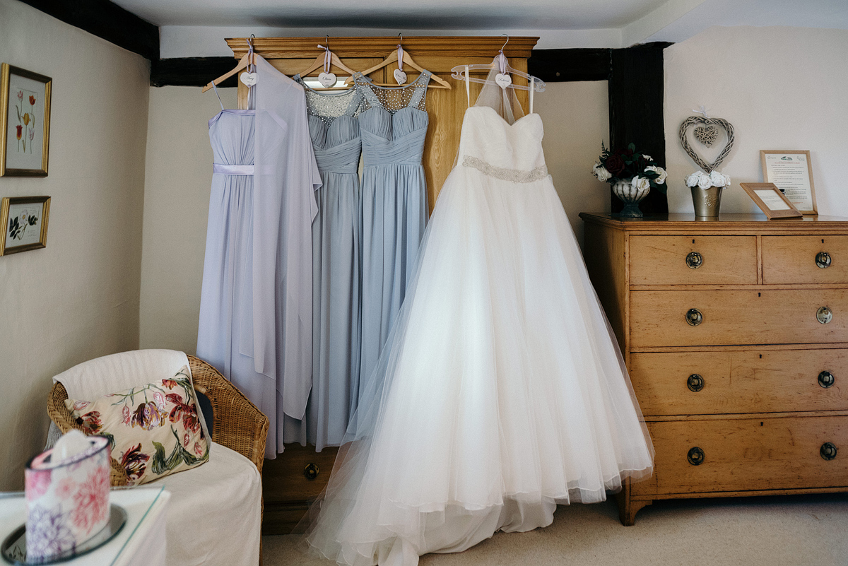 Bride and bridesmaid dresses hung on dresser.
