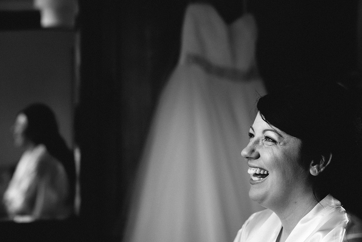 Close up of bride laughing, her reflection and dress in background.