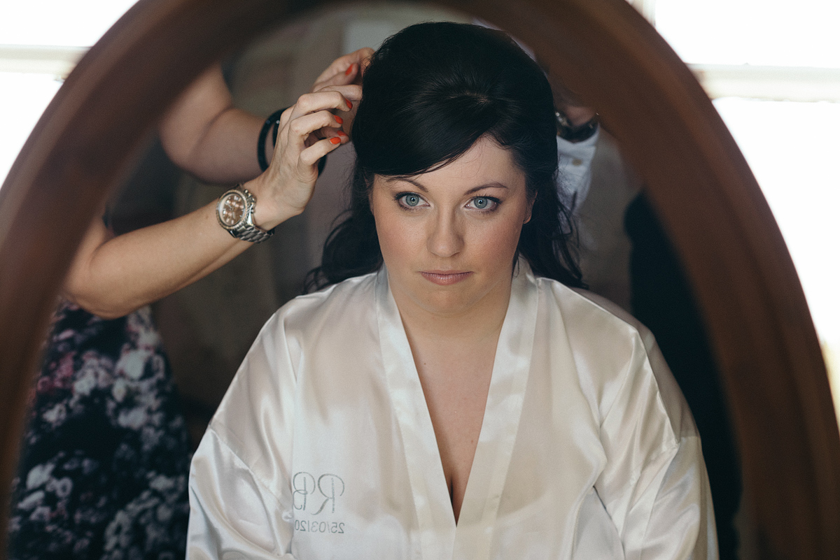 Bride looking into vanity mirror as stylist pins her hair.
