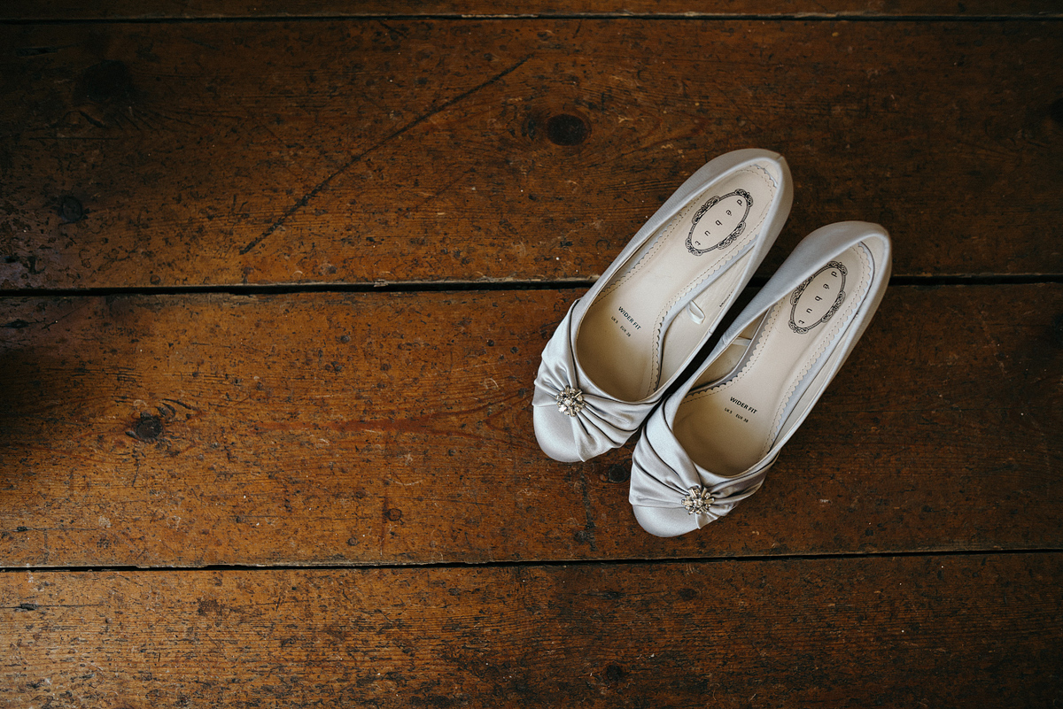 Brides shoes placed on the hardwood floor.