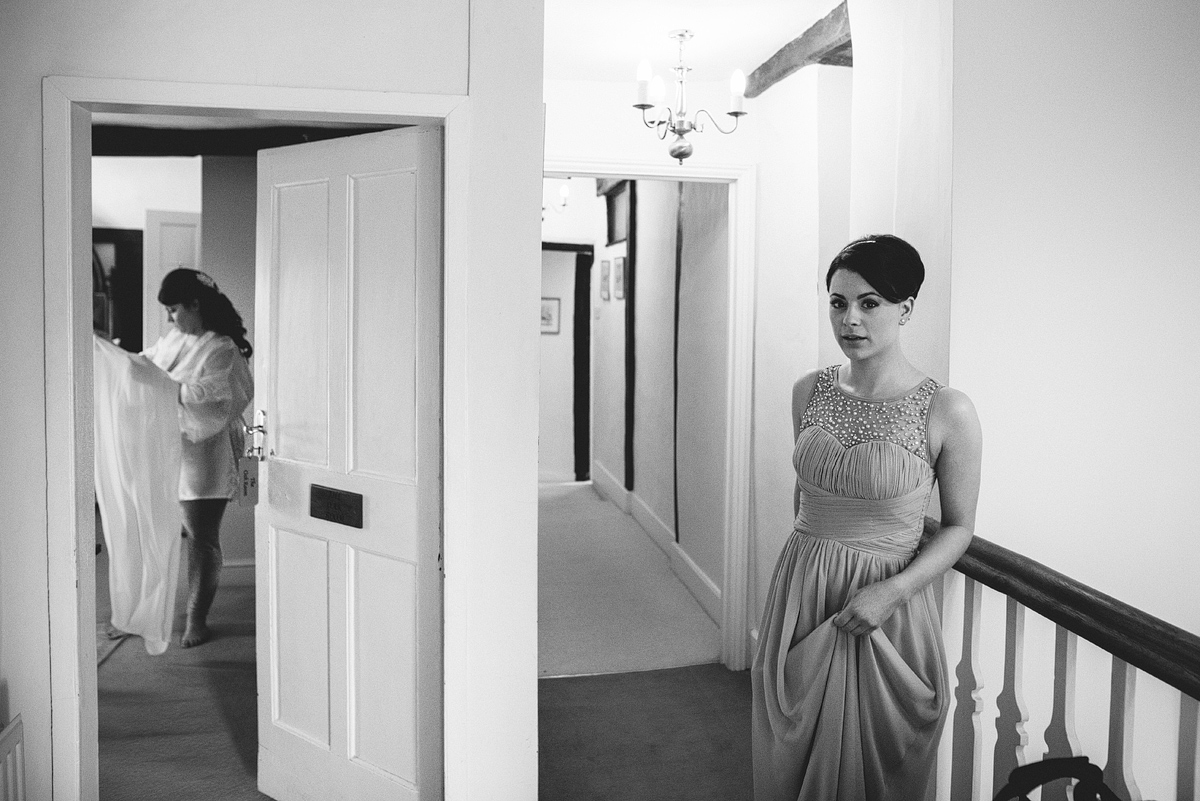 Bridesmaid waiting outside while bride behind half open door looks at dress