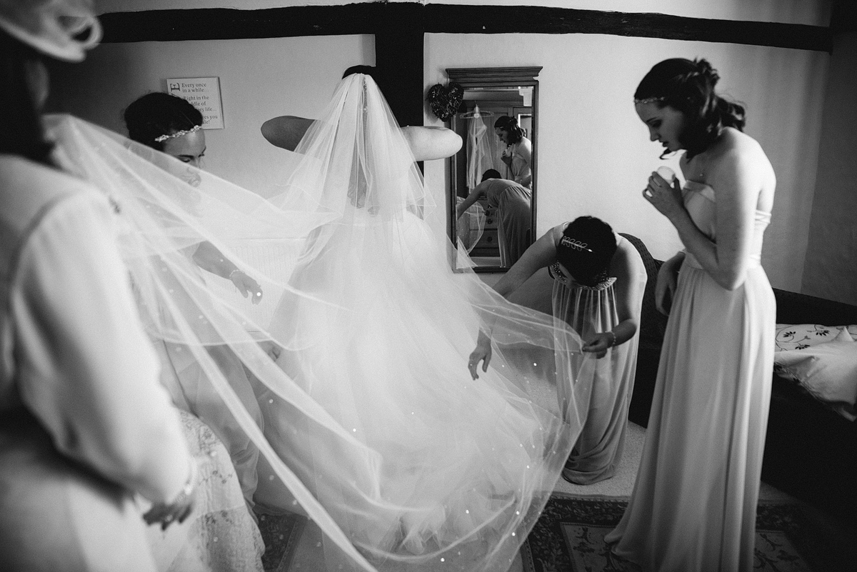 Veil and train being placed on bride