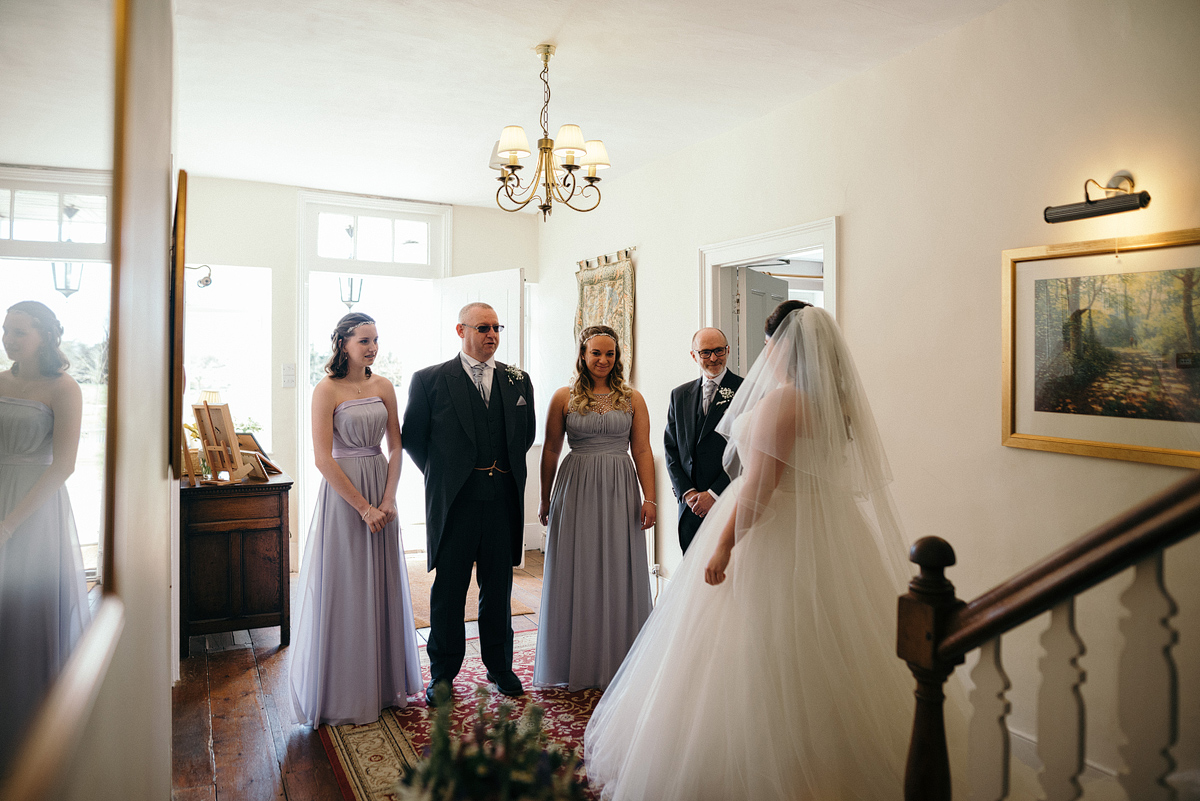 Bride standing in front of bridemaids and fathers.