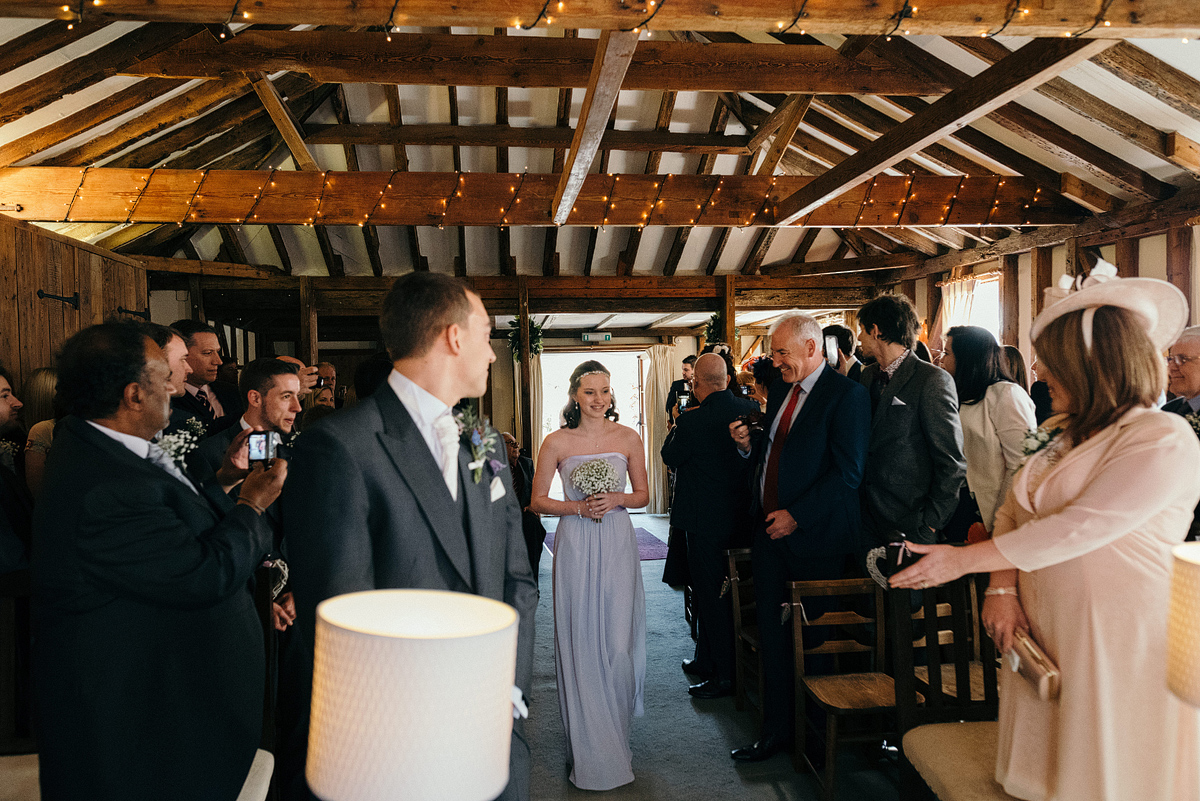 Bridesmaid walking down aisle as wedding ceremony begins.