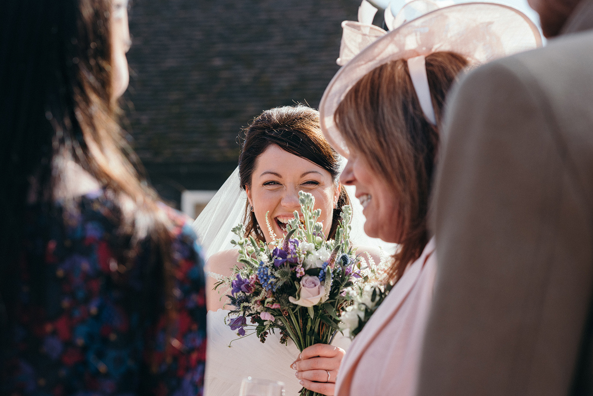 Bride laughing through her bouquet outside
