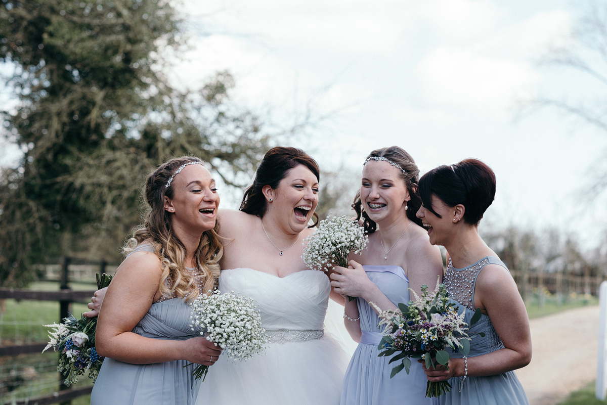 Bridesmaids and bride standing together laughing.