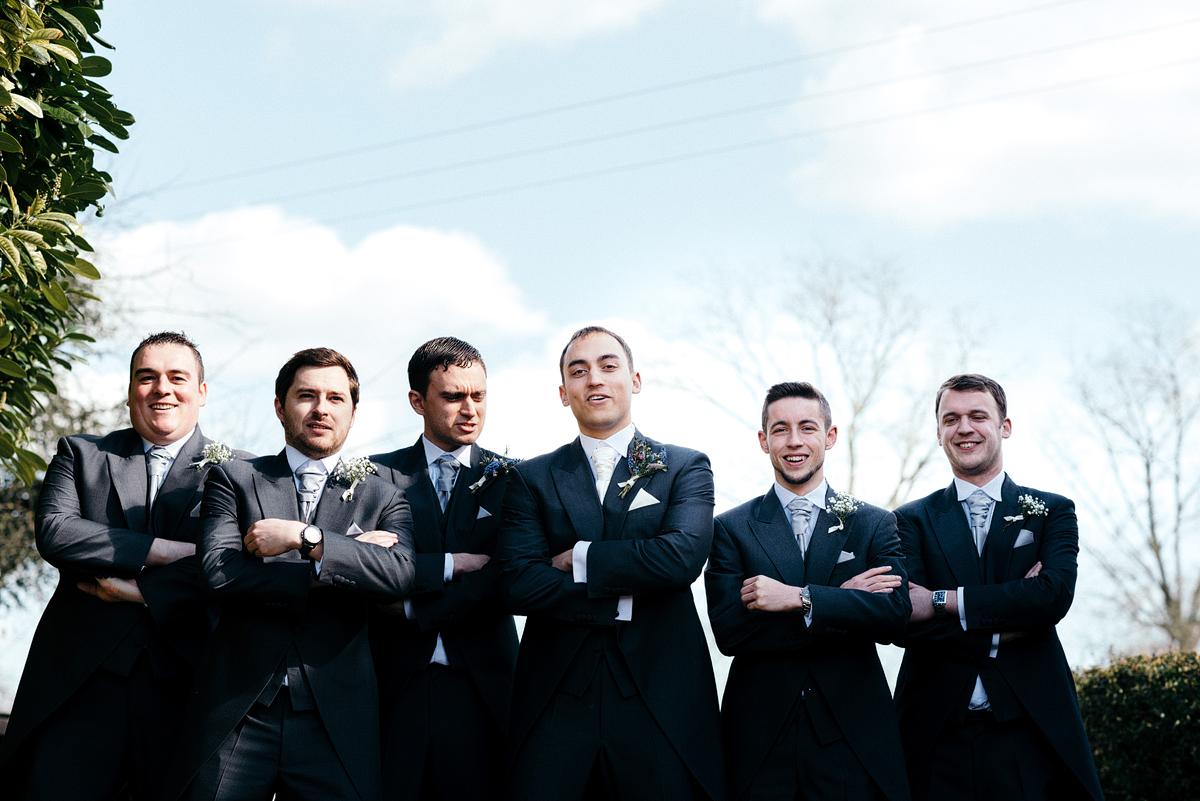 Groom and ushers standing in line, arms crossed