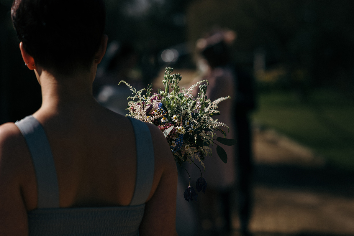 Bridesmaid, back to front, holding bouquet