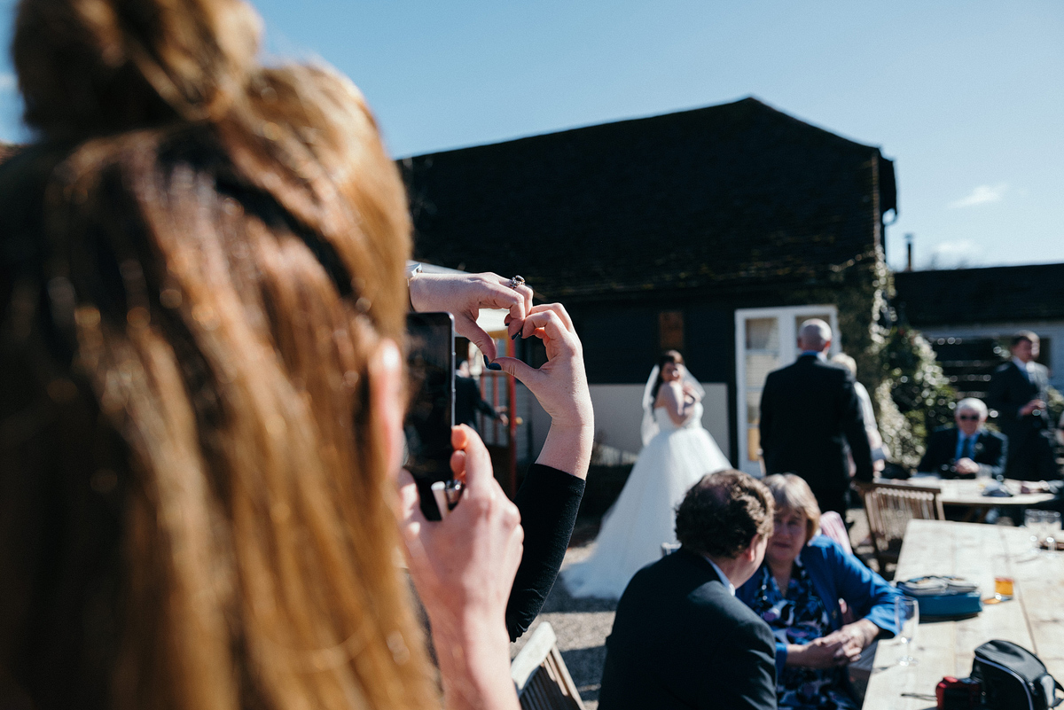 Guest taking photo of bride while second guest makes a heart shape