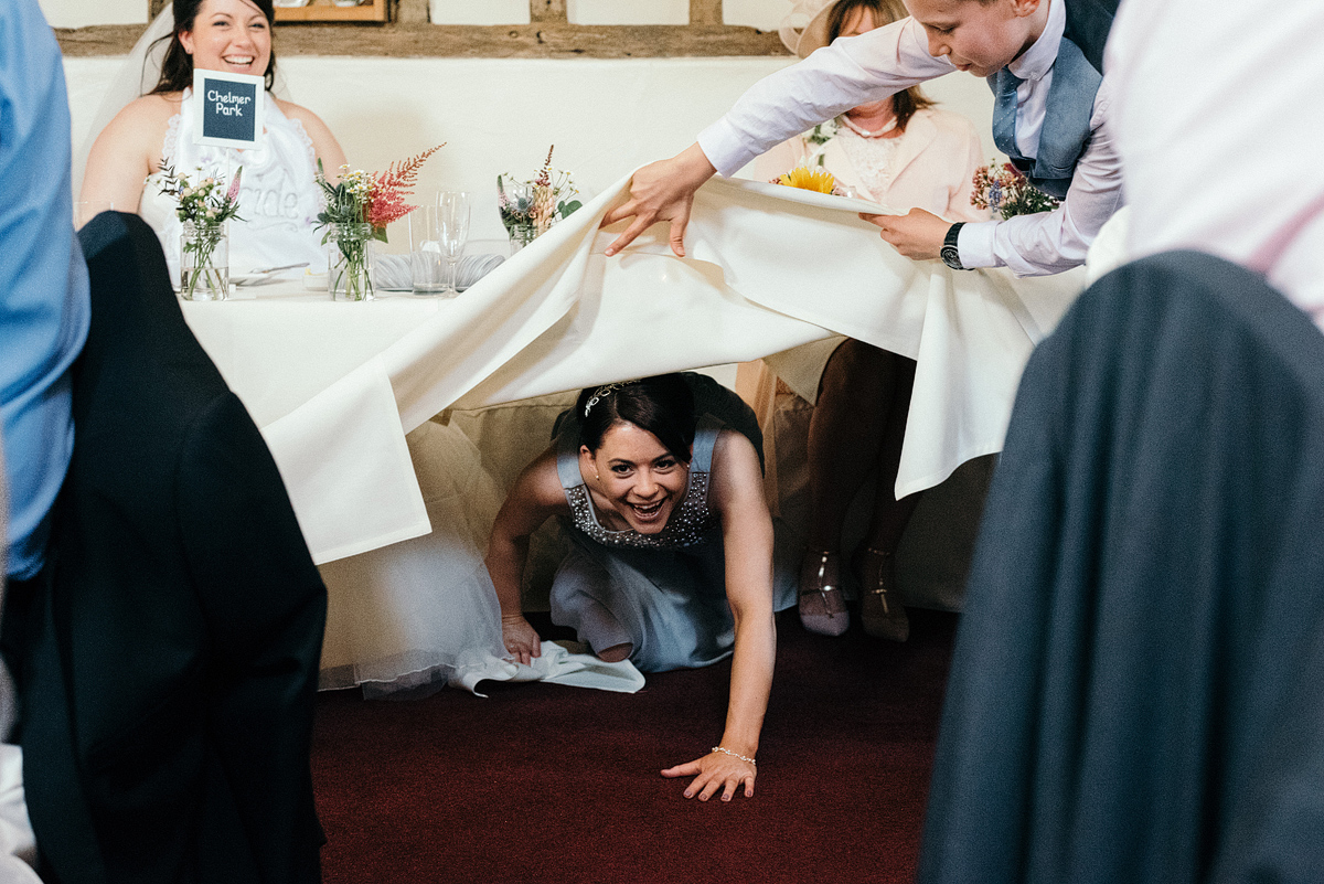 Bridesmaid laughing crawling under table.