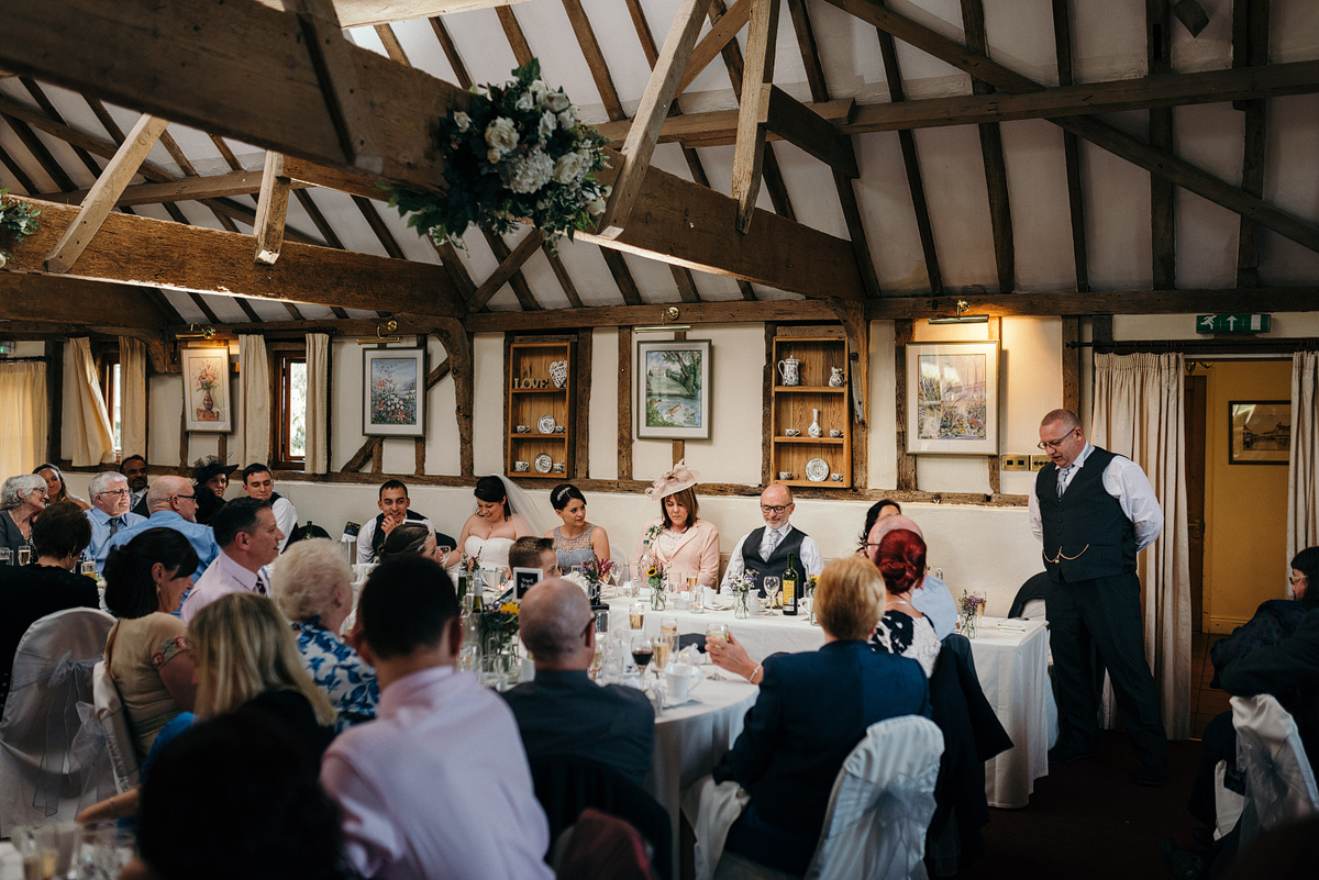 Father of bride standing giving toast at table