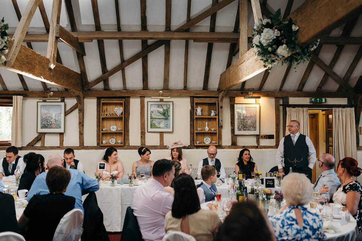 Father of bride giving speech at head of reception table