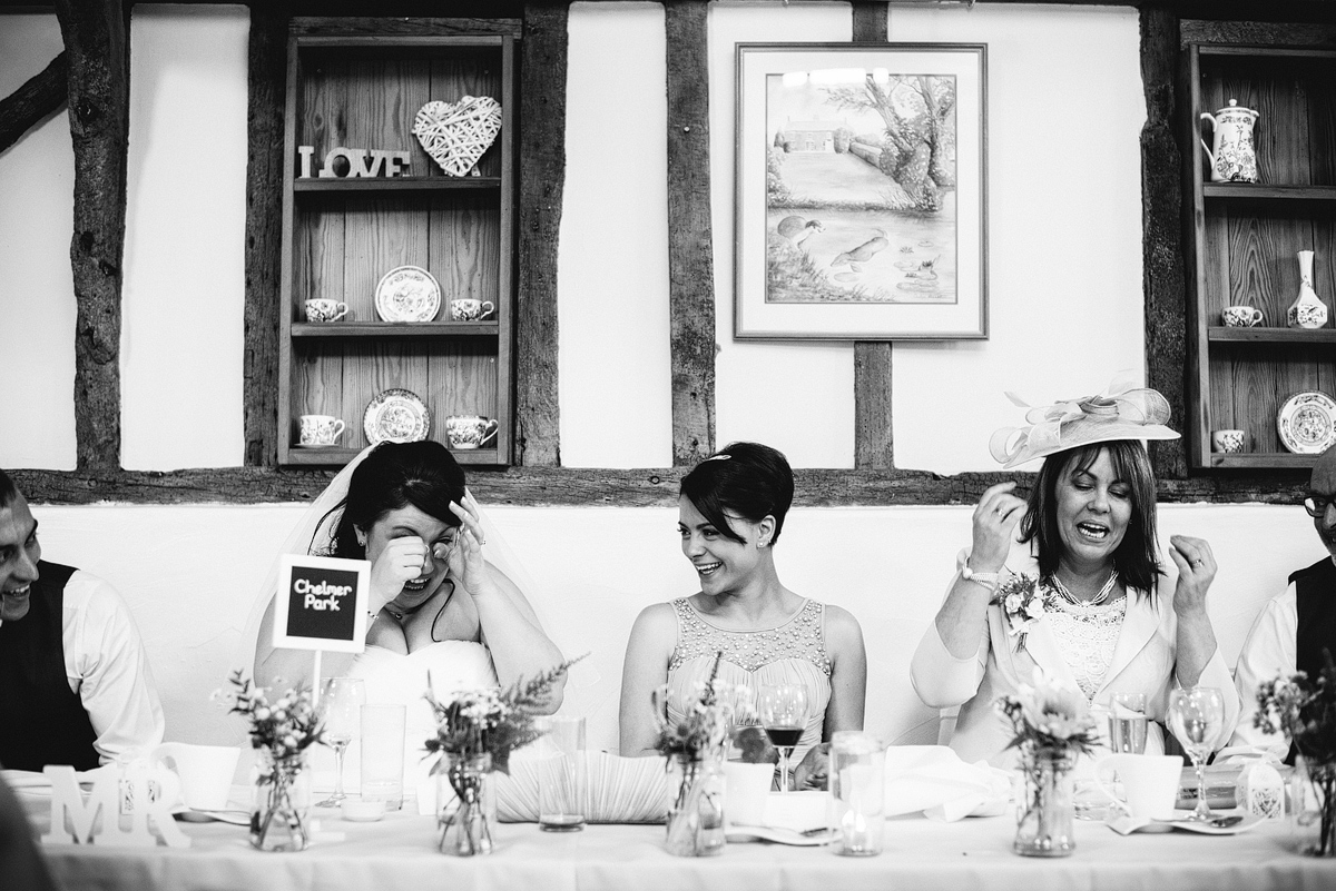 Mother of bride speaking, bride laughing wiping away tears