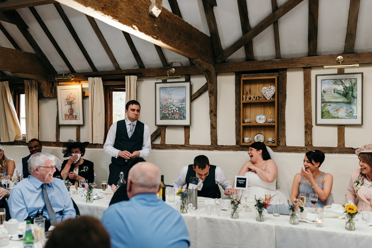 Guest makes toast as bride, groom, and guests laugh.