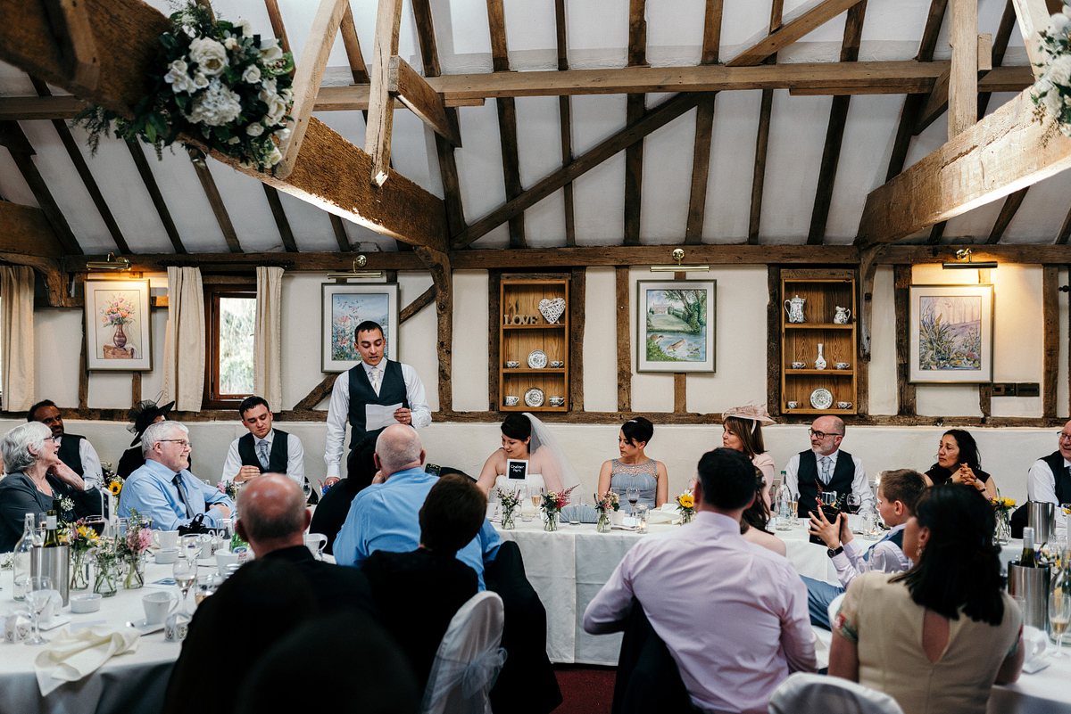 Tables of guests listening as groom makes speech