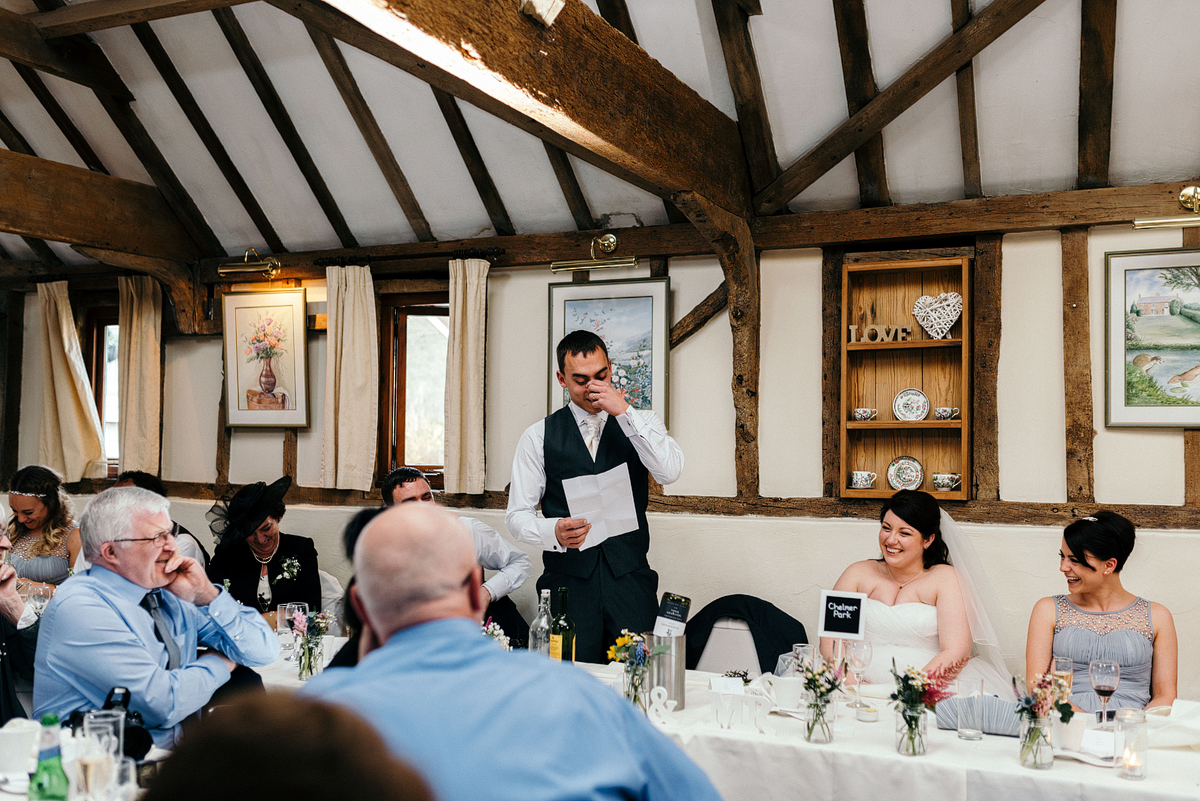 Groom reading speech while guests listen, laughing