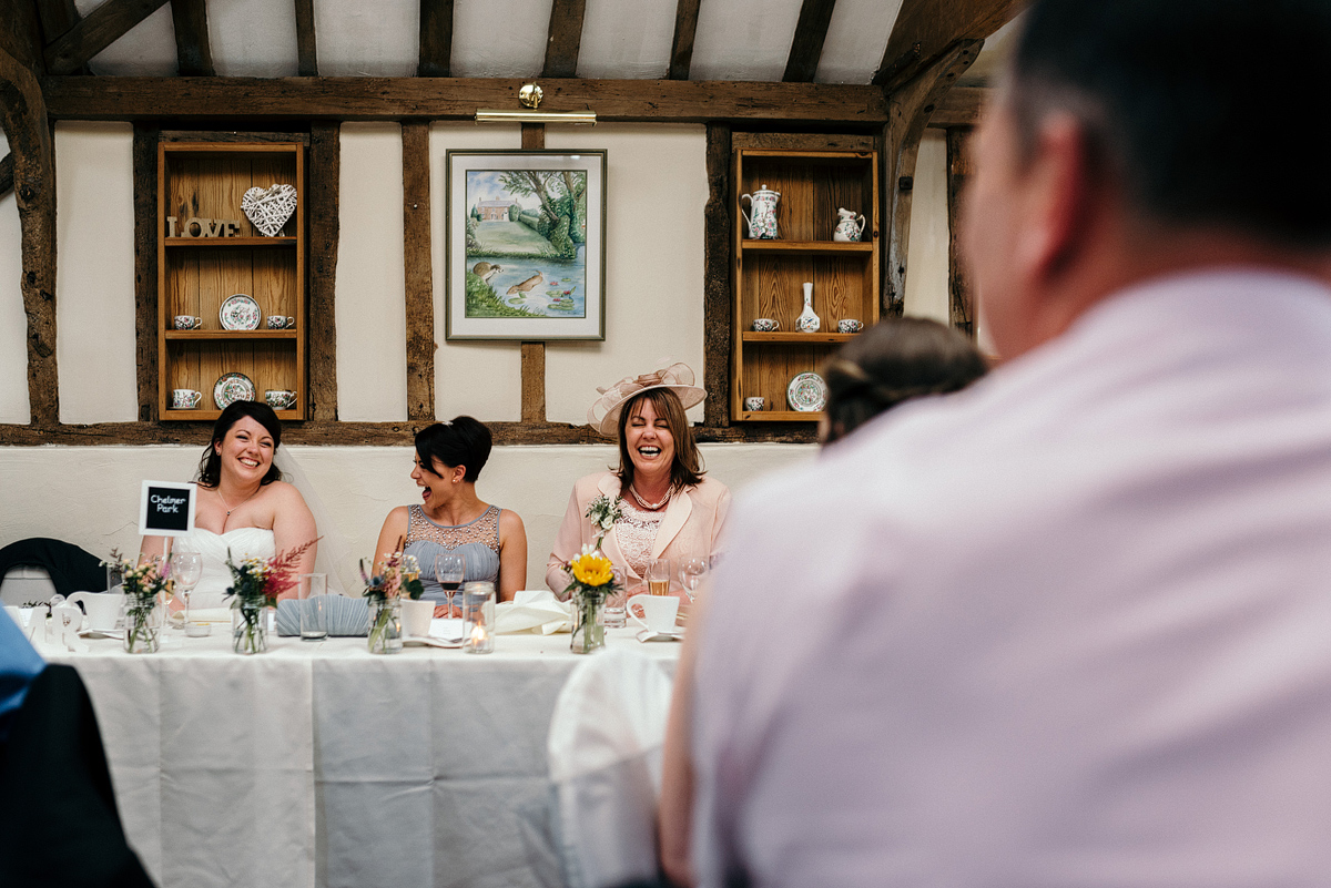 Bride and guests laughing at table.