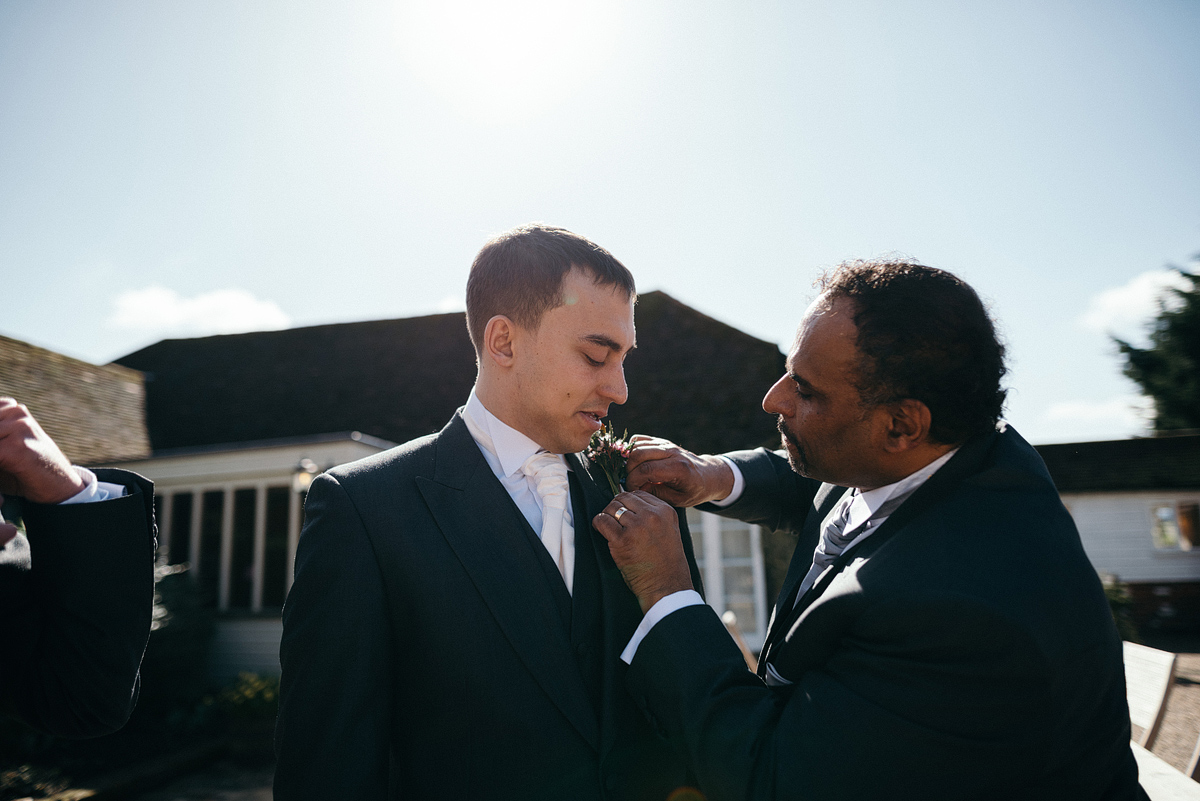 Father putting Boutonniere on groom's suit