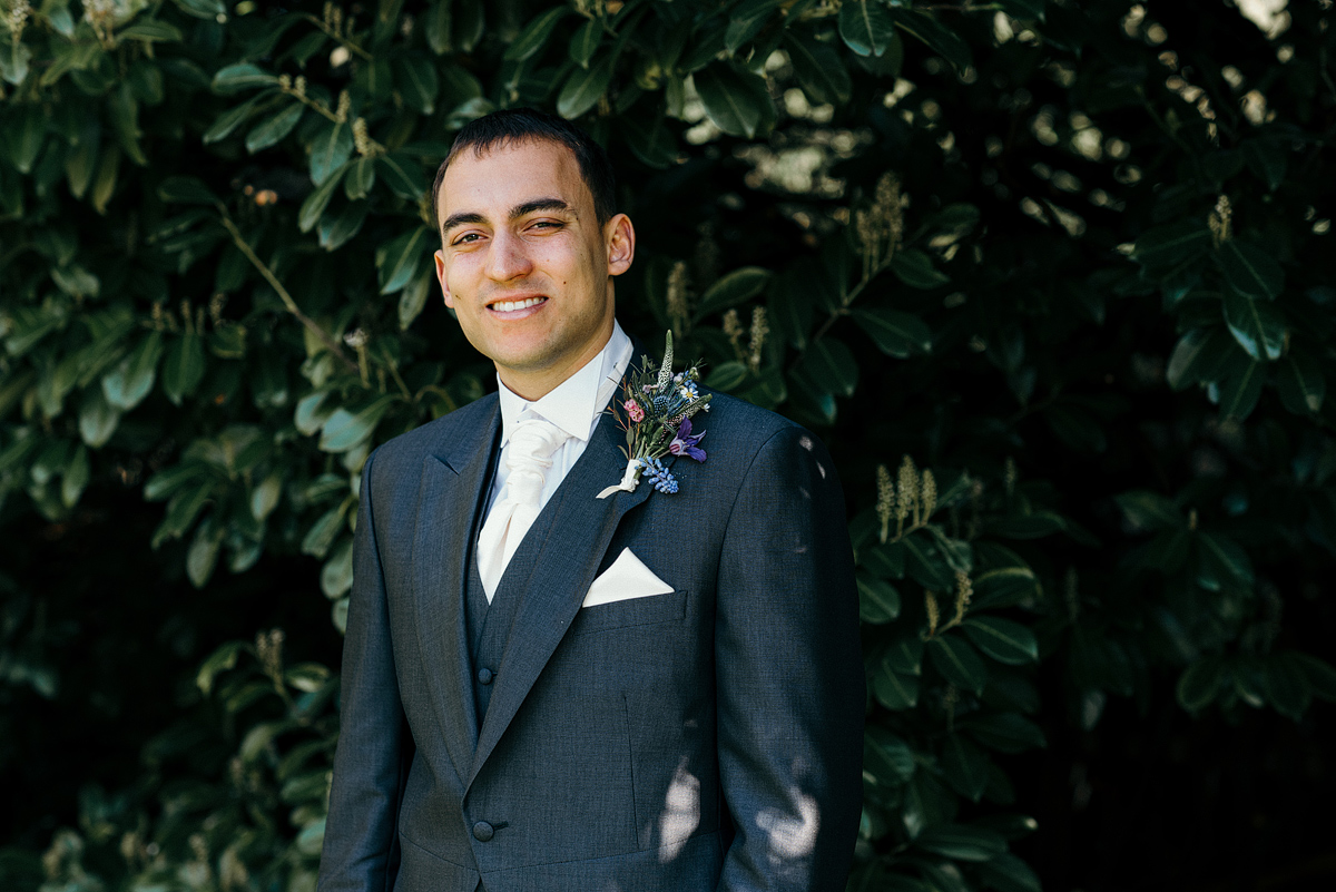 Groom smiling in shade under trees.