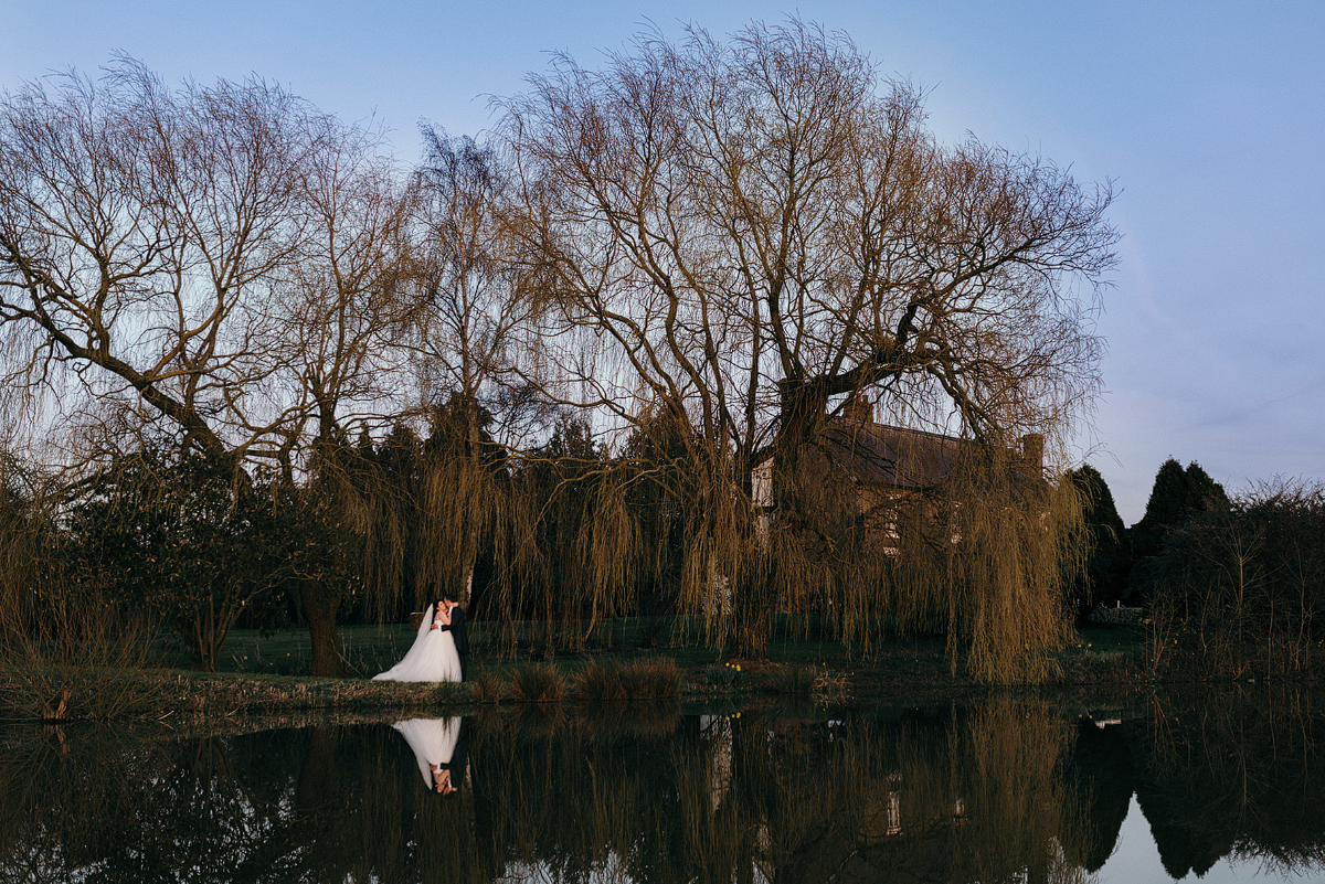 Bride and groom embracing outside by lake and trees