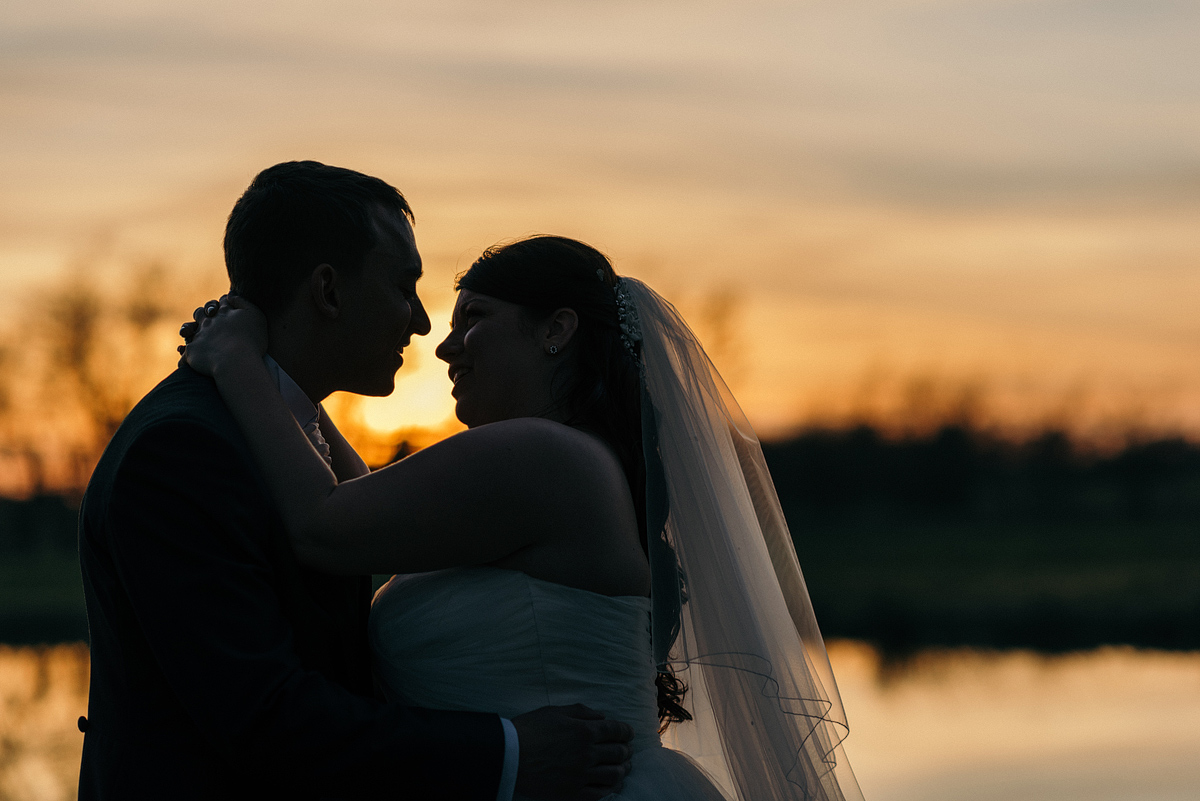 Bride and groom embrace as the sun sets.