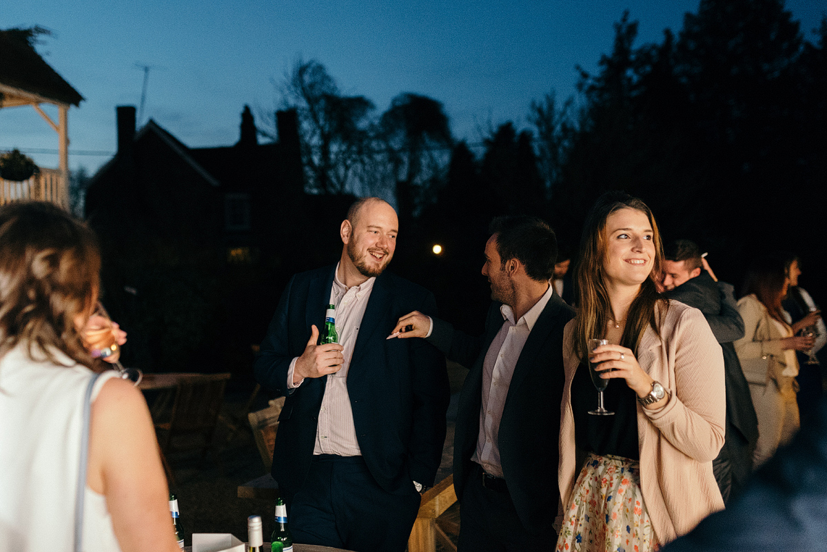 Guests smiling and talking outside while holding drinks