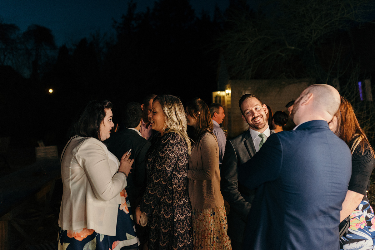 Groups of guests smiling and talking outside.